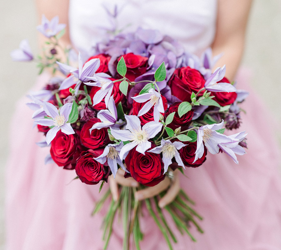 8f8daa5680a2 En färgglad, romantisk brudbukett i rött och lila. Innehåller rosor med  klematis och hortensia.